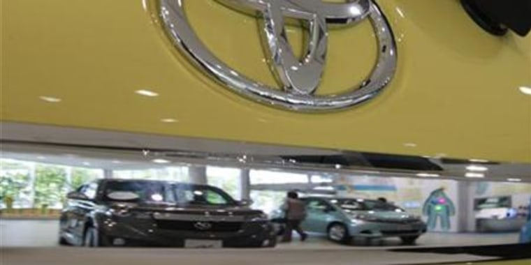 A visitor is reflected in a Toyota Motor Corp's vehicle displayed at the company's showroom in Tokyo