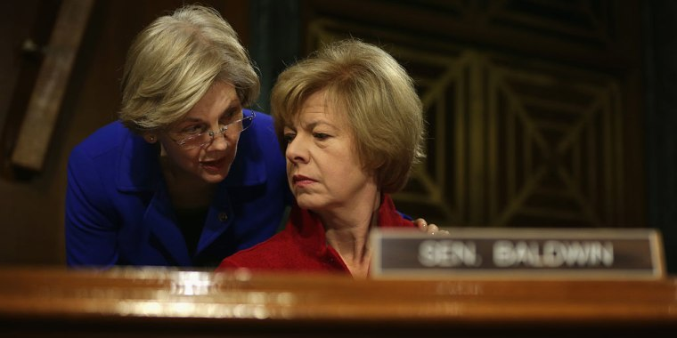 U.S. Sen. Elizabeth Warren (D-MA) (L) talks to Sen. Tammy Baldwin (D-WA) (R) during a hearing before Senate Health, Education, Labor and Pensions Committee February 10, 2015 on Capitol Hill in Washington, DC.