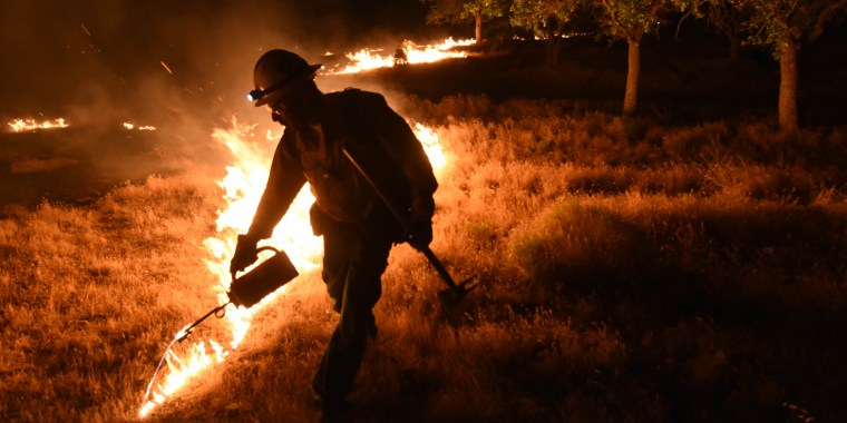 A Kern County firefighter sets a backfire by a wildfire burning near Lake Isabella, Calif. on Friday, June 24, 2016.  Dozens of homes burned to the ground as a wildfire raged over ridges and tore through rural communities in central California, authorities said.