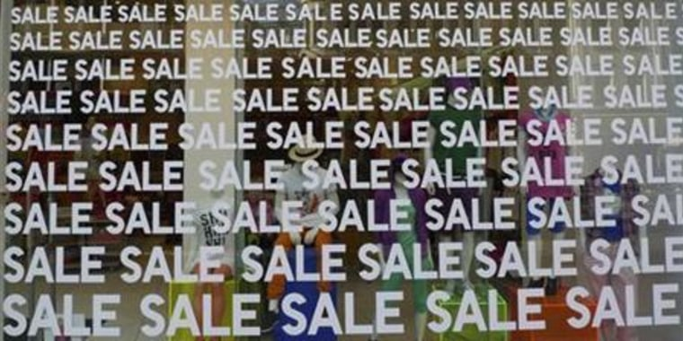 A store front window is covered with the world 'sale'  at retail clothing shop during the London summer sales period