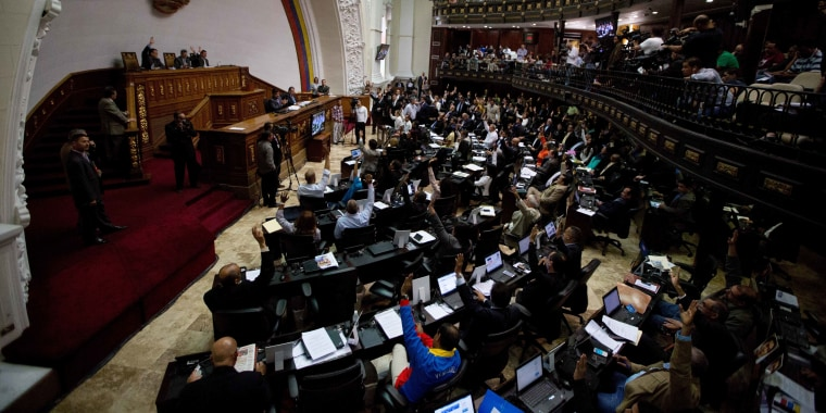 In this Jan. 14, 2016 photo, Venezuelan National Assembly lawmakers vote during a session in Caracas, Venezuela.