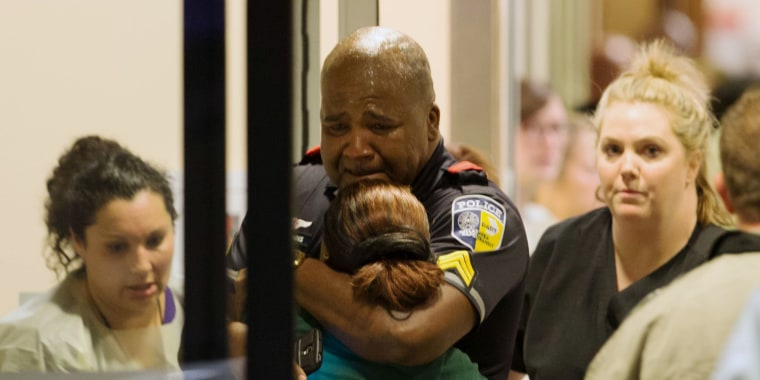 Image: A Dallas Area Rapid Transit police officer receives comfort at an emergency room