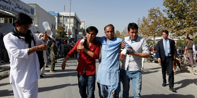 Image: Men help an injured man outside a hospital after a suicide attack in Kabul