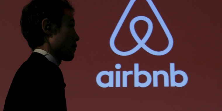 Image: A man walks past a logo of Airbnb after a news conference in Tokyo
