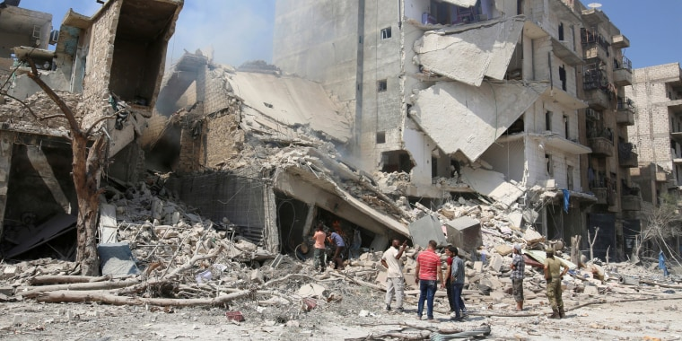 Image: A file photo shows men inspecting a damaged site after double airstrikes on the rebel held Bab al-Nairab neighborhood of Aleppo