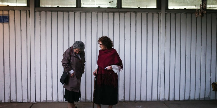 """In this Sept. 5, 2016 photo, Violeta Zuniga, 83, right, and Martha Perez, 80, members of the """"Cueca Sola"""" dance group, talk before performing at a school in Santiago, Chile."""