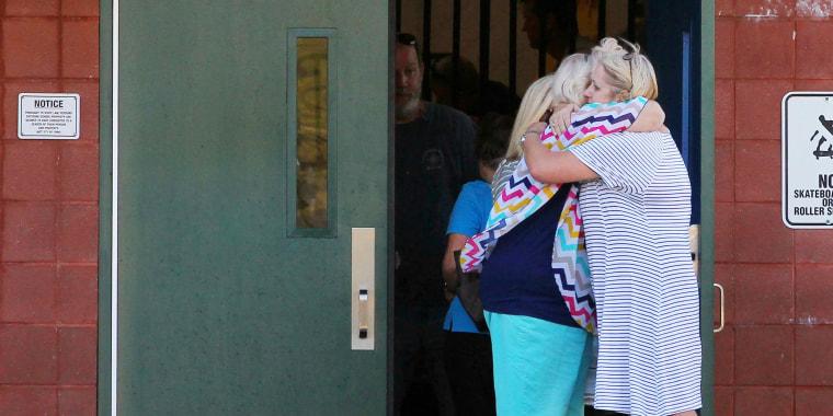 Image: Teachers hug outside Townville Elementary School