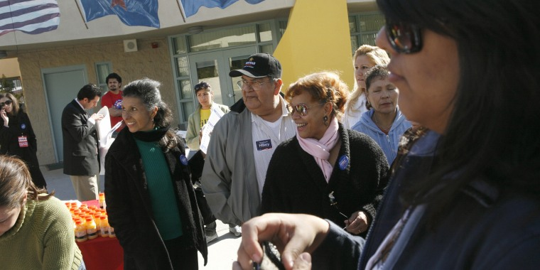David Morales and Silvia Raposo (C) line up for registration at a caucus precinct 19 January 2008 in East Las Vegas, Nevada.