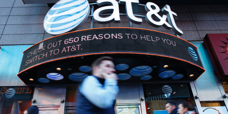 Image: People walk past an AT&T store in New York