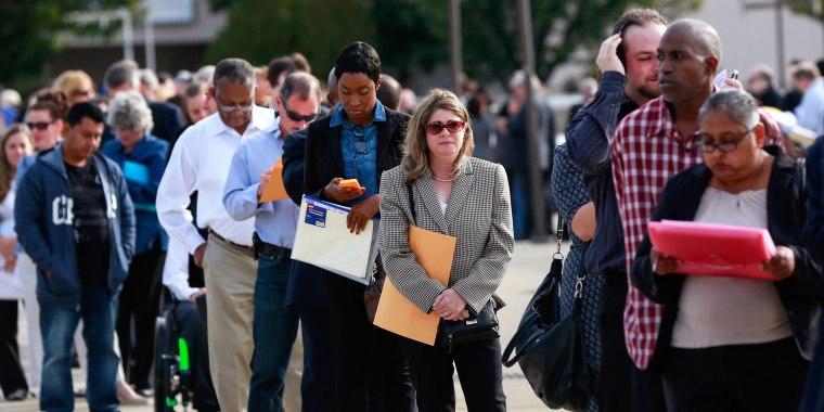 Image: People wait in line to enter the Nassau County Mega Job Fair at Nassau Veterans Memorial Coliseum in Uniondale, New York