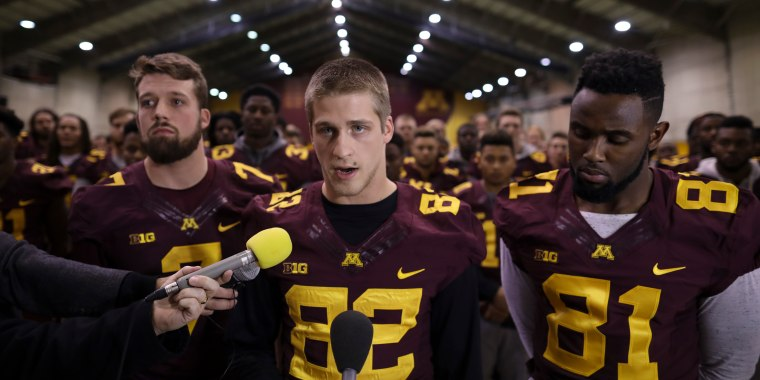 University of Minnesota wide receiver Drew Wolitarsky, flanked by quarterback Mitch Leidner, left, and tight end Duke Anyanwu stands in front of other team members as he reads a statement on behalf of the players in the Nagurski Football Complex in Minneapolis, Minn., Thursday night, Dec. 15, 2016.