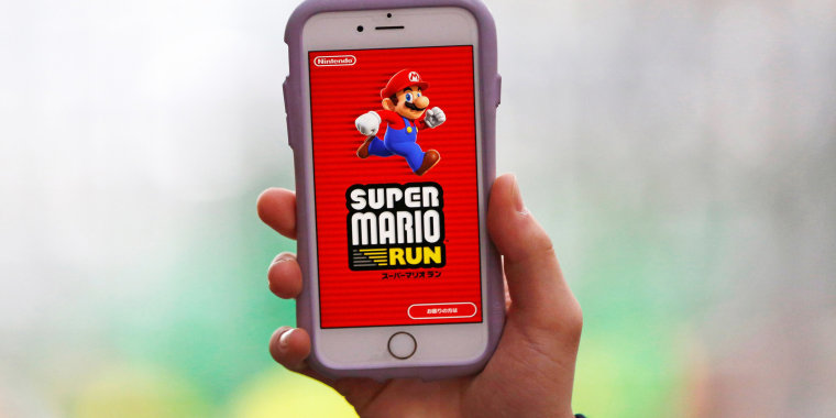 "Image: A person poses to display Nintendo's ""Super Mario Run"" game on a mobile phone in Tokyo, Japan"