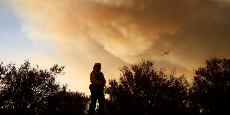 Image: A fire captain watches a fire's movement as an aircraft flies overhead during the Pilot Fire near in San Bernardino, California