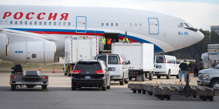 Image: Vehicles pull up to a Russian aircraft to load freight