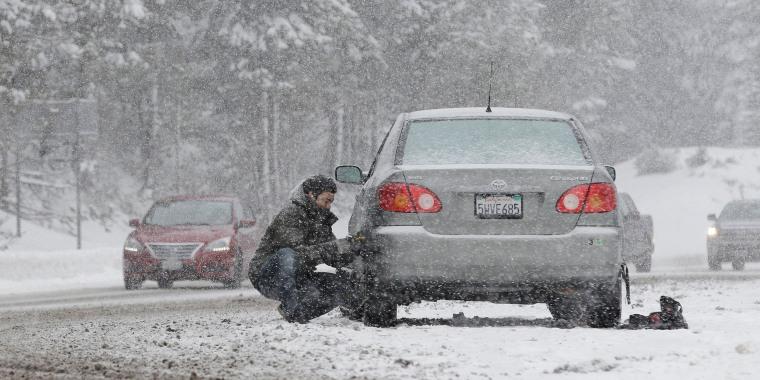 Image: A motorist puts on snow chains near Echo Summit, Calif.