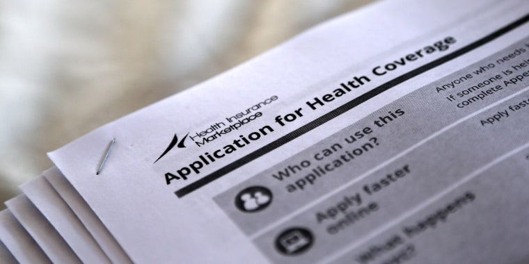 Image: The federal government forms for applying for health coverage are seen at a rally held by supporters of the Affordable Care Act.