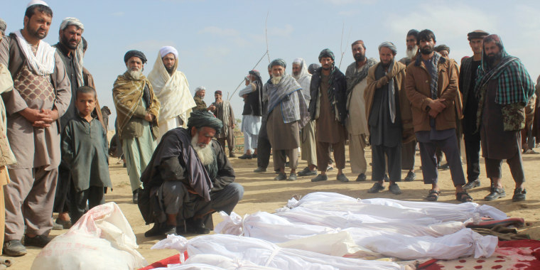 Image: Afghan villagers gather around several victims' bodies who were killed during clashes between Taliban and Afghan security forces