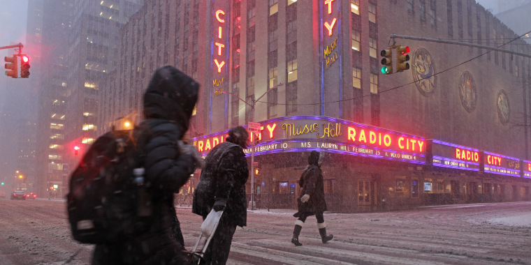 Image: Pedestrians walk through blowing snow in front of Radio City Music Hall