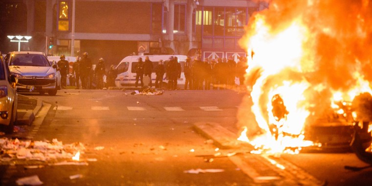 Image: Police face protesters as a car burns in Bobigny, Paris, Saturday.