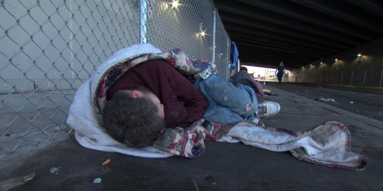 Image: A homeless person lays in the street in Everett, Wash.