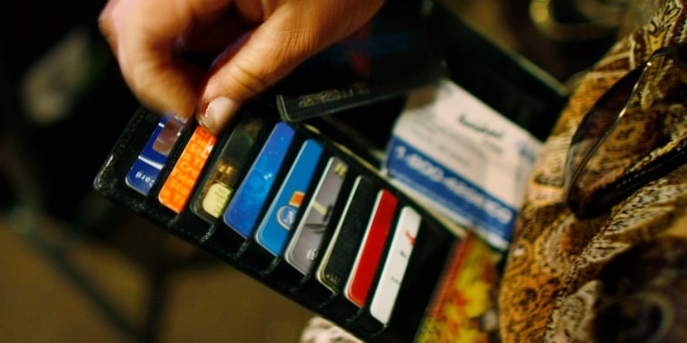 Woman looks in her wallet for credit cards