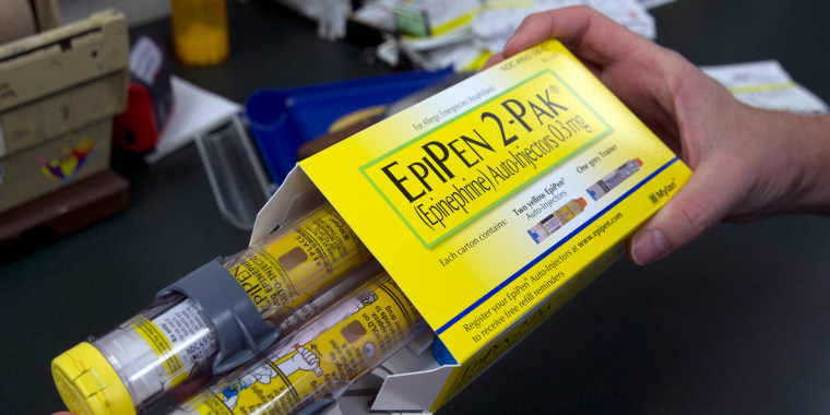 Image: A pharmacist holds a package of EpiPens epinephrine auto-injector