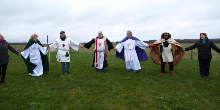 Image: Pendragon, druids and all the other visitors hold hands and form a circle around Stonehenge