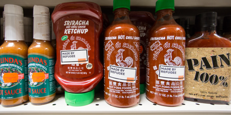 "A ""Made By Refugee"" sticker on a bottle of Sriracha hot sauce."