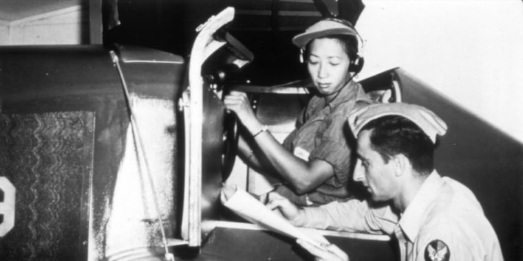 Hazel Lee reviewing her flight records in the cockpit.