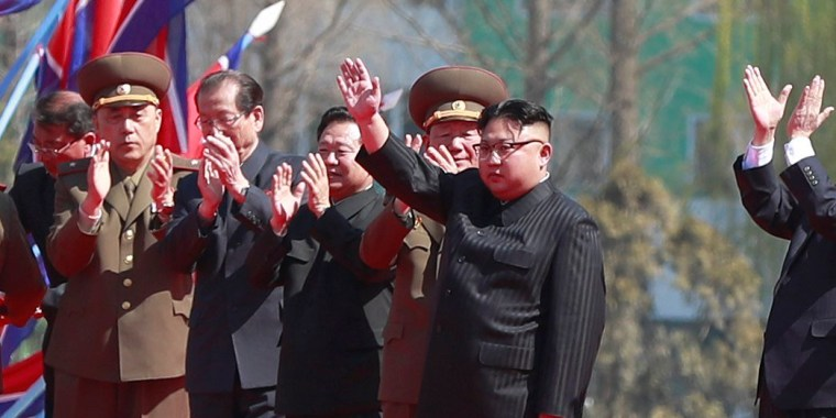 Image: Kim Jong-un waves during the official opening of a new housing project.