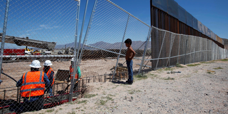 Image: A boy looks at U.S. workers building a section of the U.S.-Mexico border wall at Sunland Park