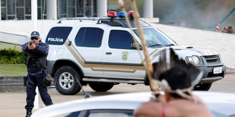 Image: Riot police points his gun at Brazilian Indians during a demonstration against the violation of indigenous people's rights, in Brasilia