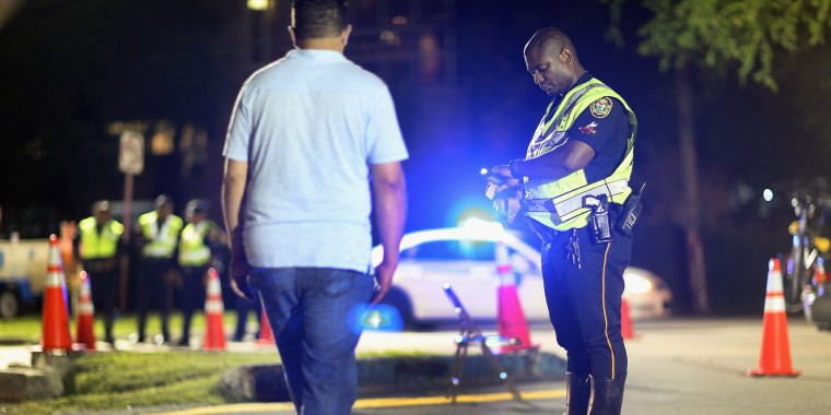 Image: A City of North Miami Beach police officer conducts a field sobriety test during a DUI checkpoint