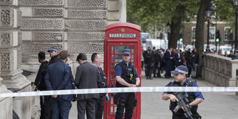 Image: A man is detained by police officers near London's Downing Street.