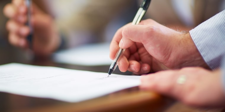 Businessman signing document in boardroom