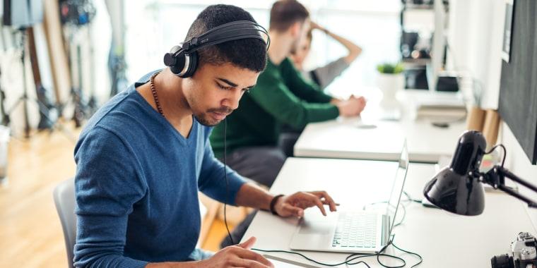Image: A man wears headphones in an office