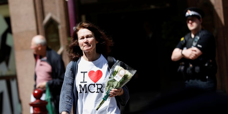 Image: A woman lays flowers for the victims of the Manchester Arena attack, in central Manchester