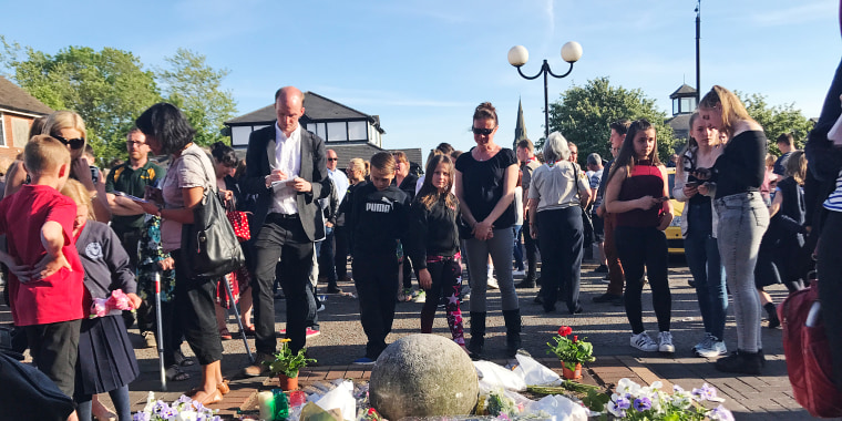 Image: Locals gather in Tarleton, England for a vigil