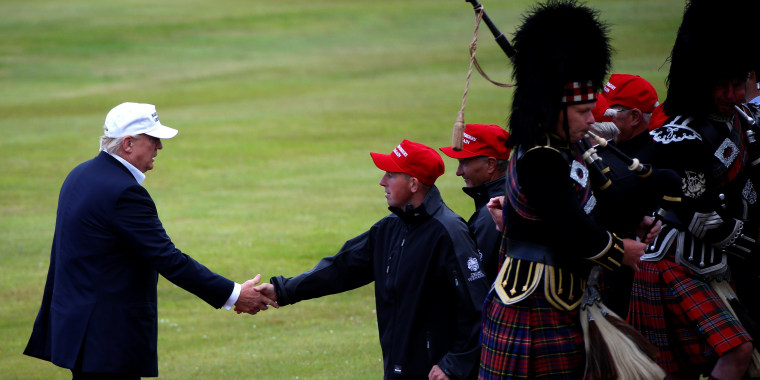 Image: Donald Trump shakes hands with a supporter after getting off his helicopter at Turnberry Golf course
