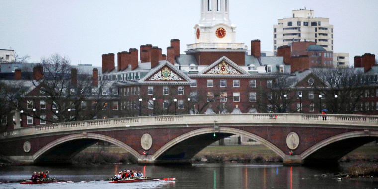 Image: Rowers paddle along the Charles River past the Harvard College campus in Cambridge