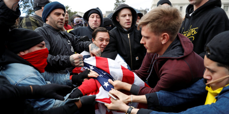 """Counter-demonstrators (L) and supporters (R) of U.S. President Donald Trump fight for a U.S. flag during a """"People 4 Trump"""" rally in Berkeley, California"""