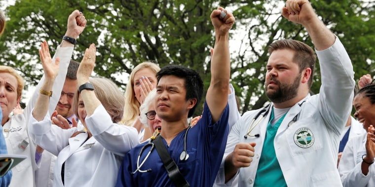 Image: Nancy Pelosi and healthcare workers react to remarks during an event protesting proposed Republican healthcare legislation
