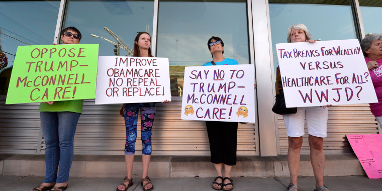 Image: Protesters wait for the arrival of Senate Majority Leader Mitch McConnell, R-Ky., at the Hardin County Lincoln Day Dinner, June 30, 2017, in Elizabethtown, Kentucky.
