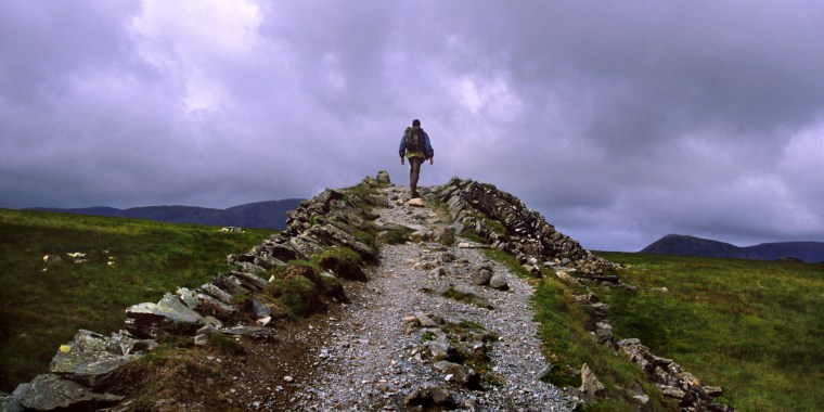 Image: A man hikes on a trail