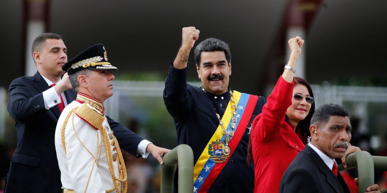 Image: Venezuela's President Nicolas Maduro and first lady Cilia Flores raise their fists during a military parade
