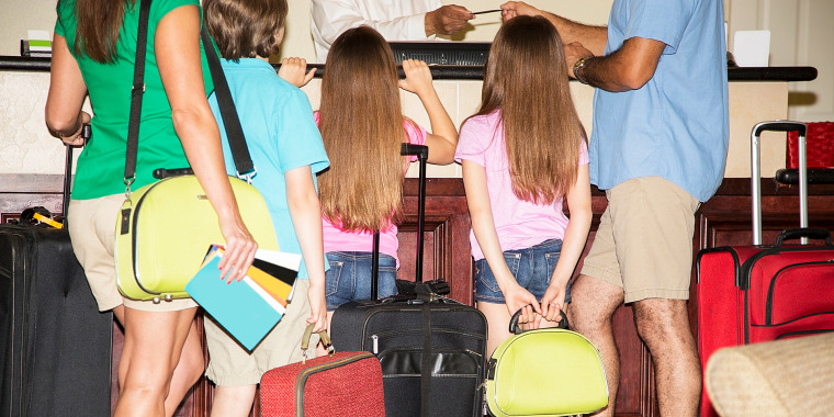 Family on summer vacation checking into hotel. Reception desk. Luggage.