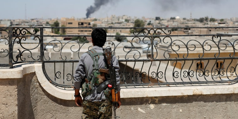Image: A Kurdish fighter from the People's Protection Units looks at a smoke after an coalition airstrike in Raqqa
