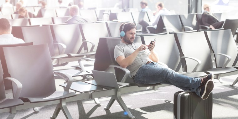 Man with headphones waiting at airport departure lounge