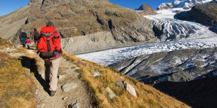 Hikers on a path with Vadret Pers, a side glacier and main Morteratsch glacier in background.