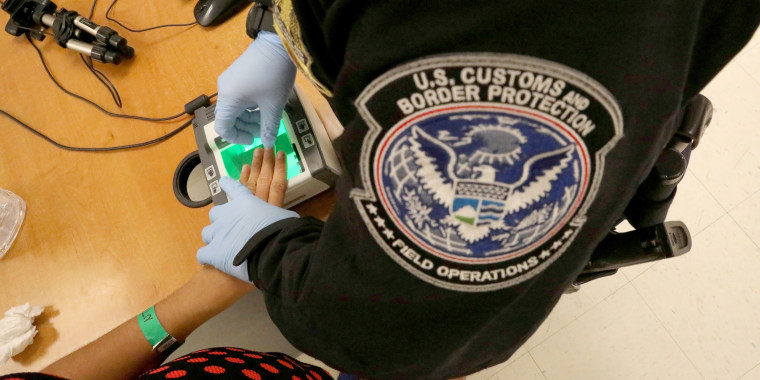 Image: A woman who is seeking asylum has her fingerprints taken by a U.S. Customs and Border patrol officer at a pedestrian port of entry from Mexico to the United States, in McAllen, Texas, May 10, 2017.